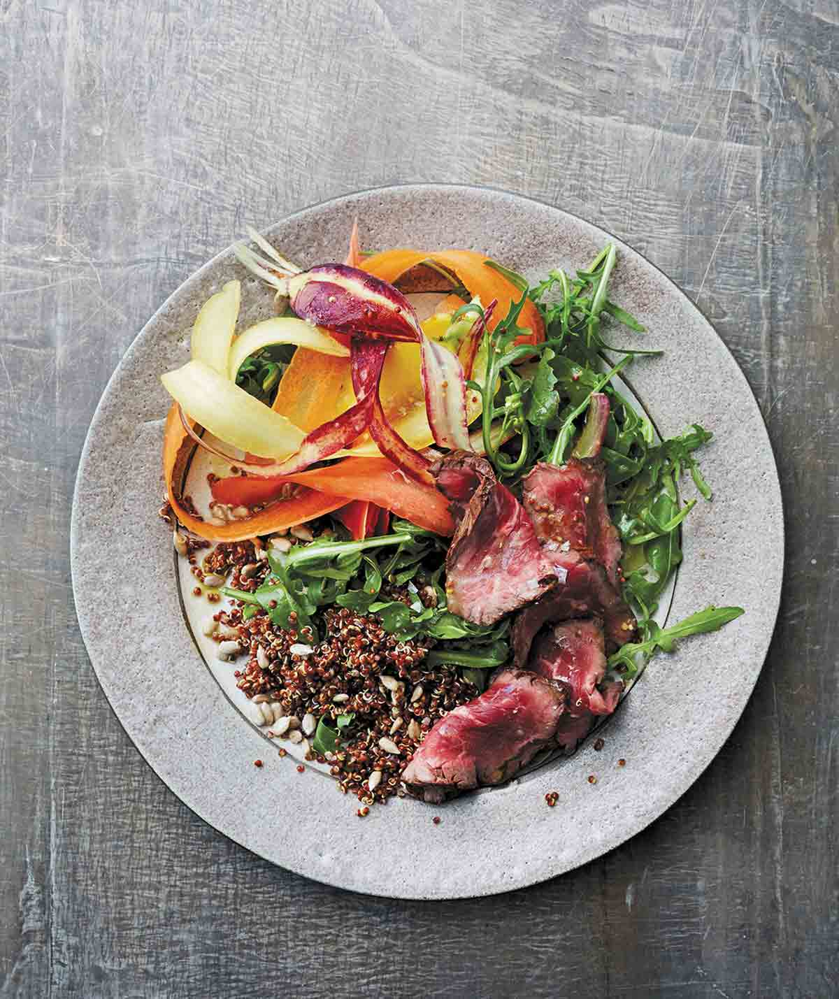 A grey plate topped with steak and quinoa salad with shaved carrots and mustard vinaigrette.