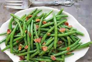 A white serving platter filled with sweet and sour green beans, topped with crumbled bacon.