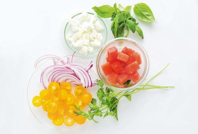 Bowls of watermelon, tomato, feta, herbs, and red onion for making the watermelon tomato feta salad.