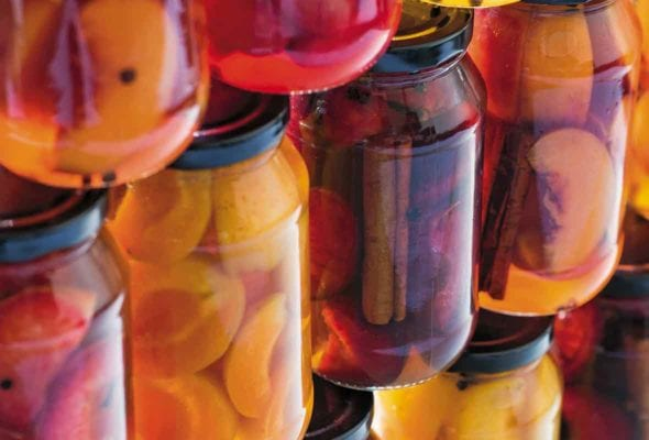 An assortment of pickled stone fruits in jars stacked on top of each other.