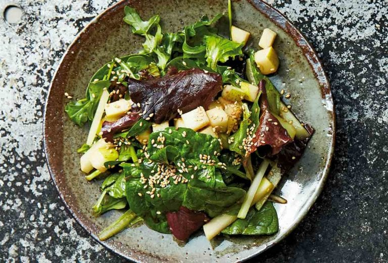 A ceramic plate filled with kohlrabi and pear salad, sprinkled with toasted sesame seeds.