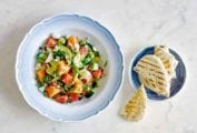 A blue and white bowl filled with melon and avocado salad with a bowl of pita beside it.