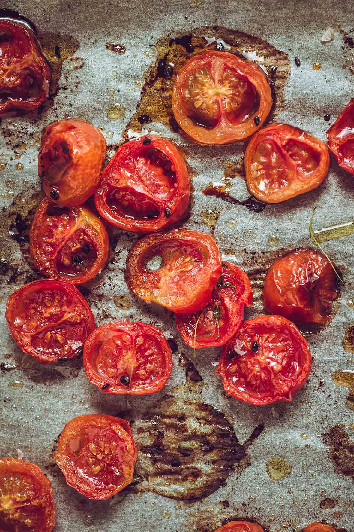 Halved slow roasted tomatoes on a piece of parchment with drops of oil and flakes of salt.