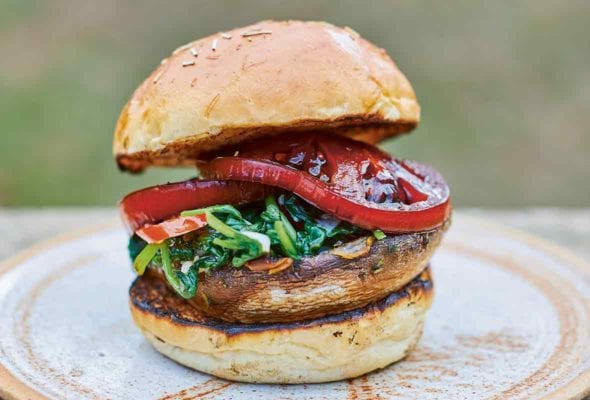 A spinach tomato mushroom burger between two toasted bun halves on a brown plate.
