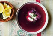 A small bowl of lemon wedges and two white bowls of deep purple summer borscht with a dollop or sour cream and sprinkling of chives in each.