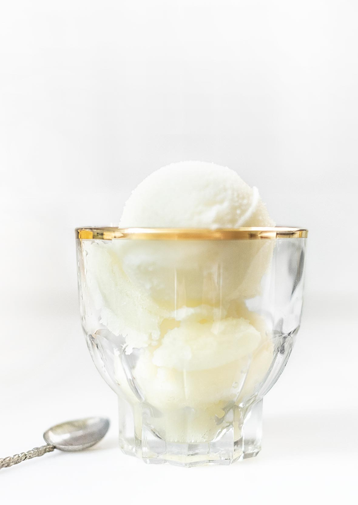 A small glass serving bowl with two scoops of tart lemon sorbet.