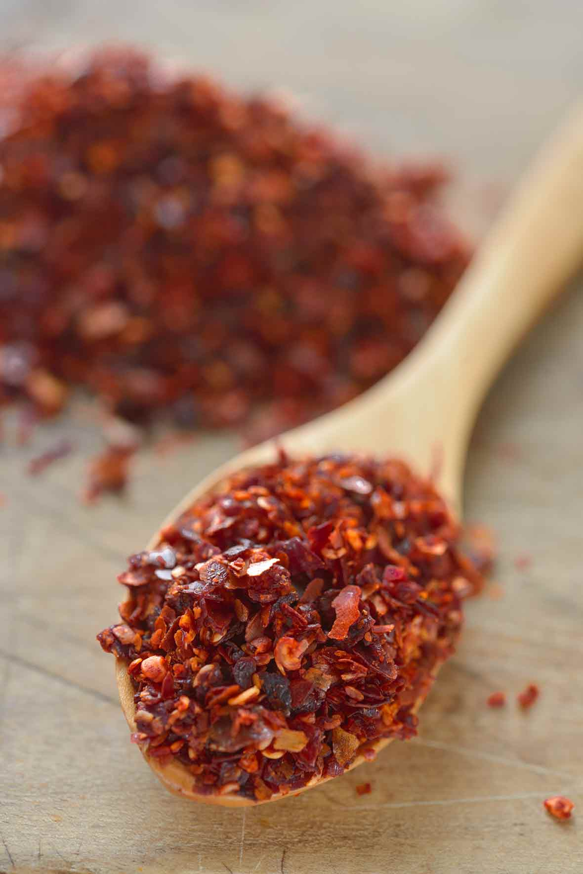 A small wooden spoon of Aleppo pepper, behind it a small pile of the pepper.