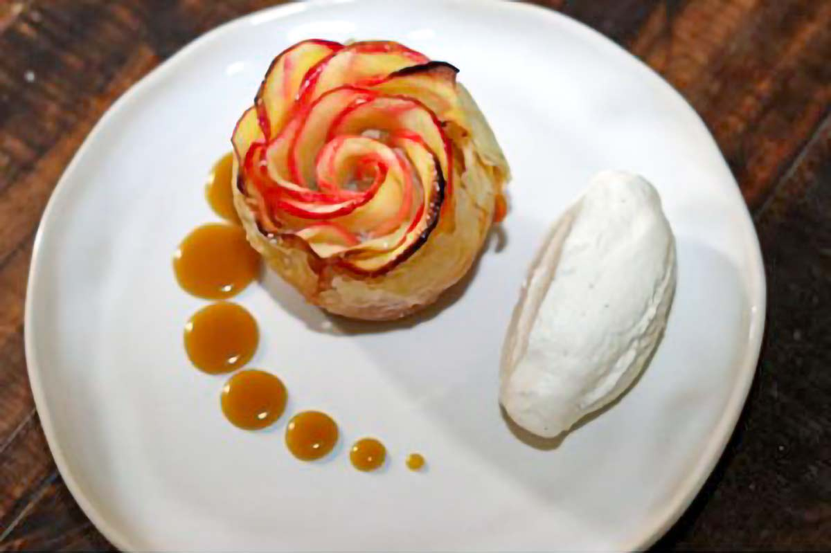 An apple rose tart, shaped to look like a rose with a scoop of ice cream beside it on a white plate.