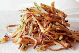 A pile of baked french fries, sprinkled with salt and fresh parsley on a paper towel.