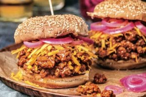 Two bourbon sloppy joes on sesame buns, topped with shredded Cheddar cheese, and pickled red onion.