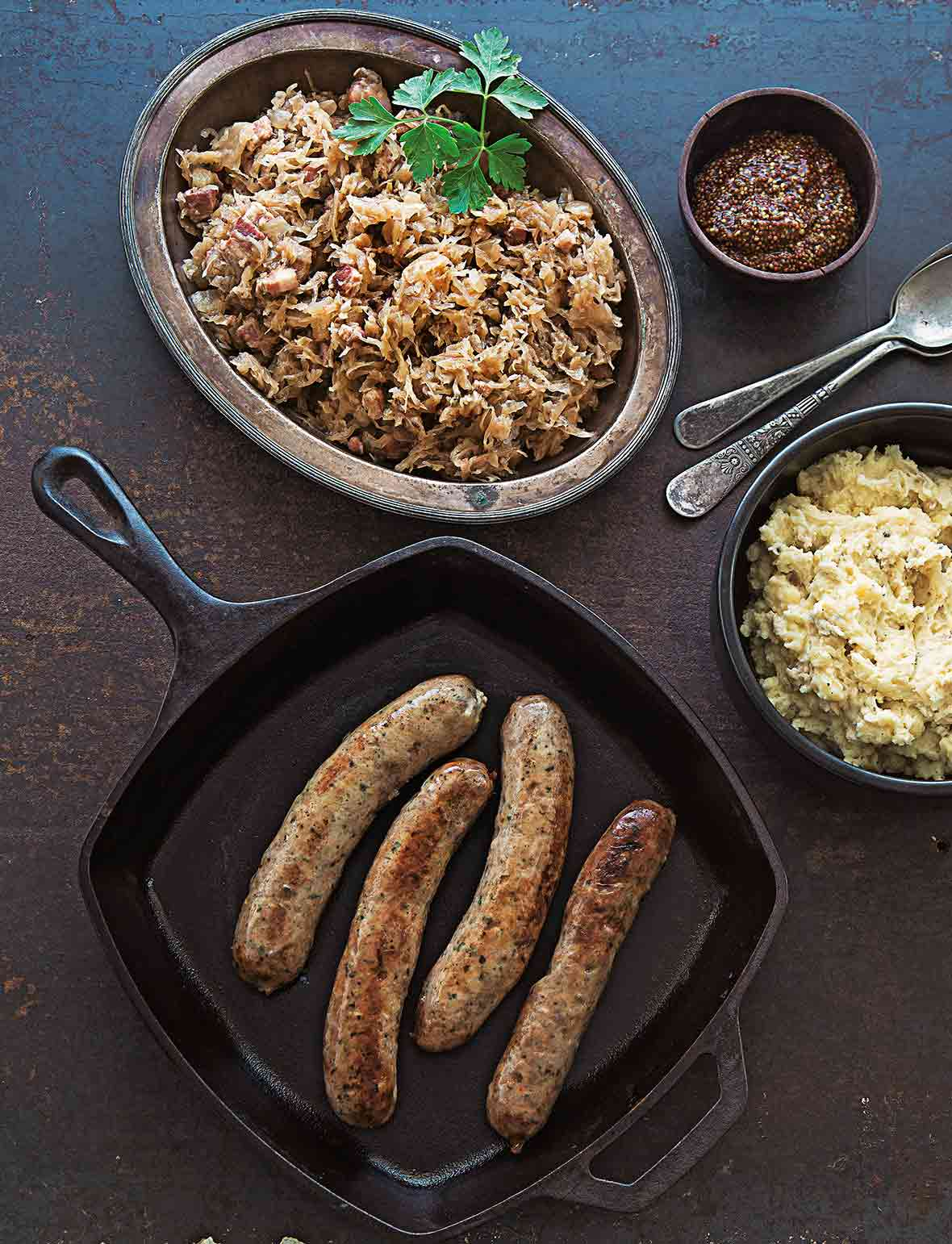 Four cooked bratwurst and sauerkraut, along with mashed potatoes, and grainy mustard in separate dishes beside the skillet containing the bratwurst.