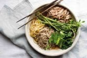 A bowl of chashu pork ramen, filled with braised pork, soba noodles, bean sprouts, peas, and bok choy, with a pair of chopsticks resting on top.
