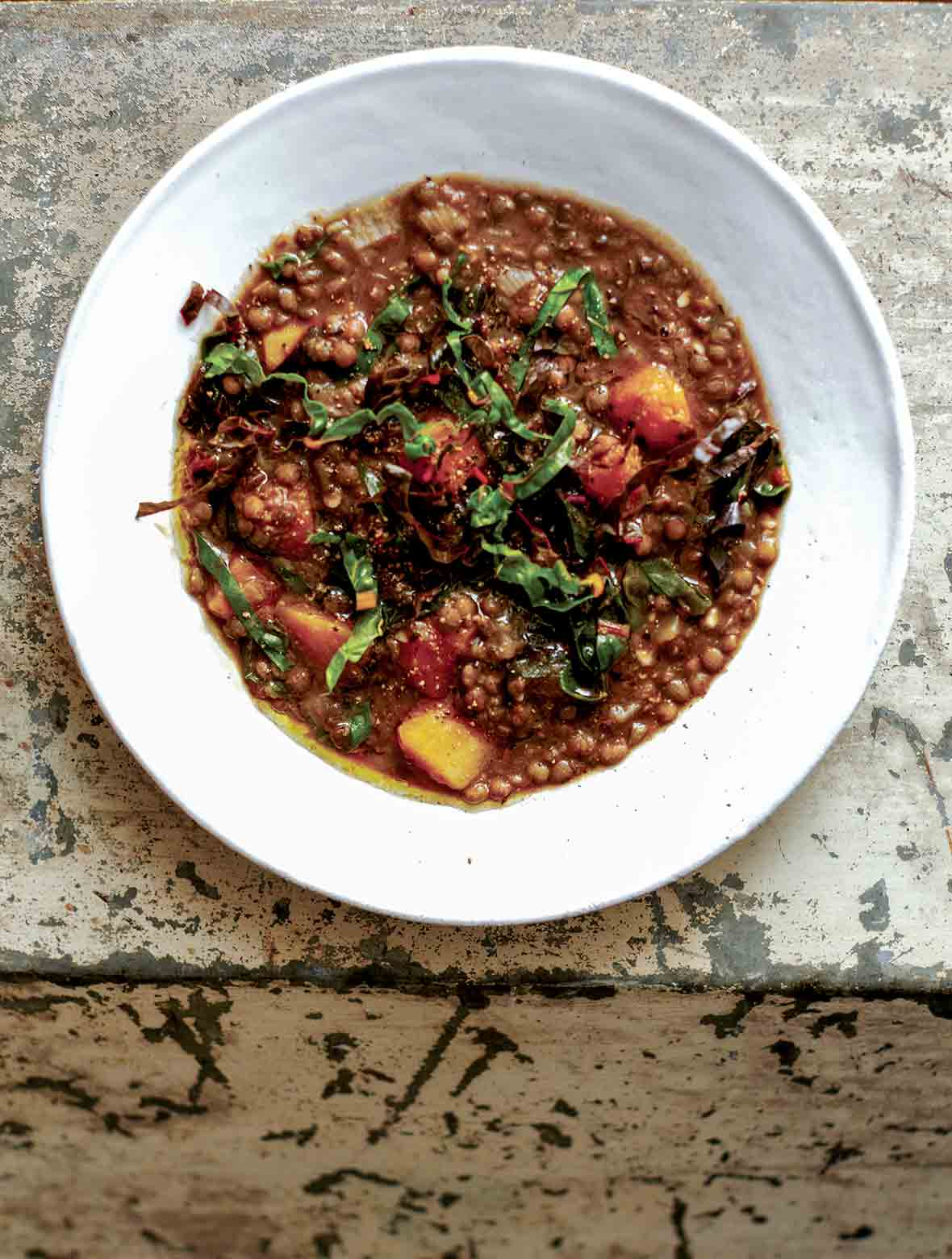 A white bowl of French lentil soup, topped with ribbons of chard.