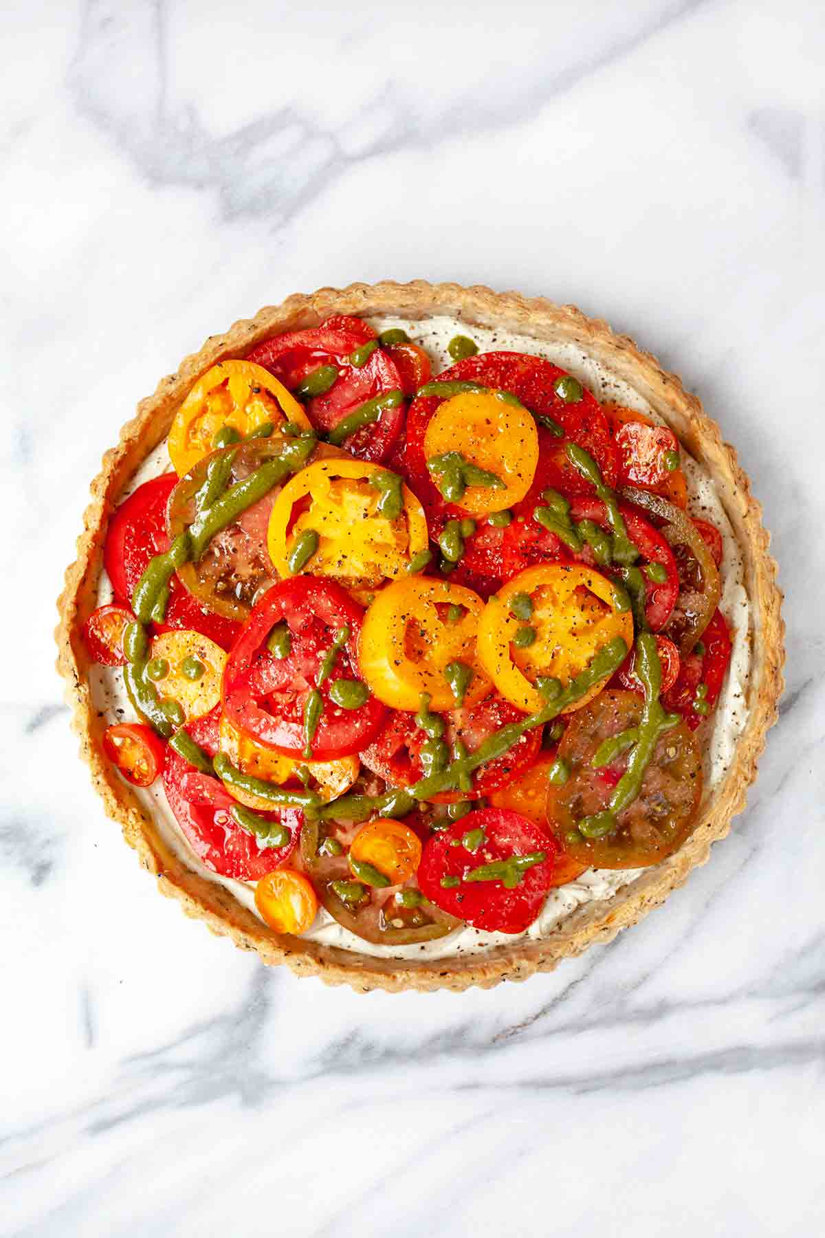 A fresh tomato tart in a herbed crust, drizzled with pesto vinaigrette.