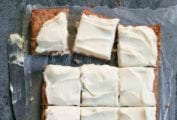 A frosted apple cake on a sheet of wax paper that has been cut into 12 squares with a knife resting beside.