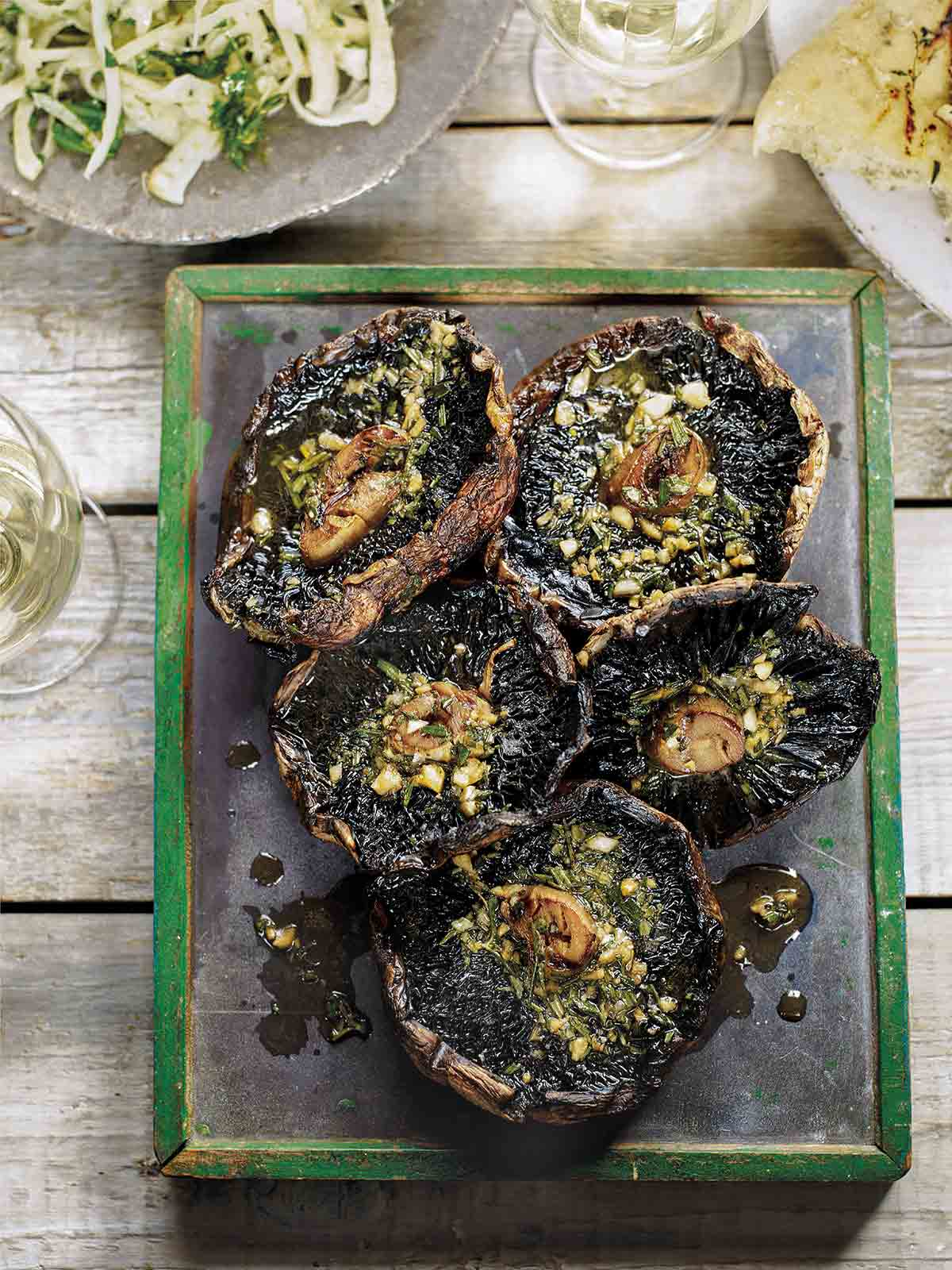A metal platter holding five grilled portobello mushrooms, topped with garlic rosemary butter.