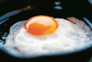 A perfect fried egg in a small black skillet.