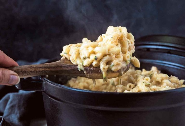 A hand using a wooden spoon to lift a scoop of macaroni and cheese with zucchini out of a cast iron pot.
