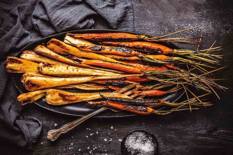 Maple glazed carrots with bourbon and parsnips on a black oval platter with a dish of salt beside it.