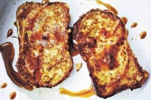 Two slices of French toast, fried until golden and drizzled with maple syrup.