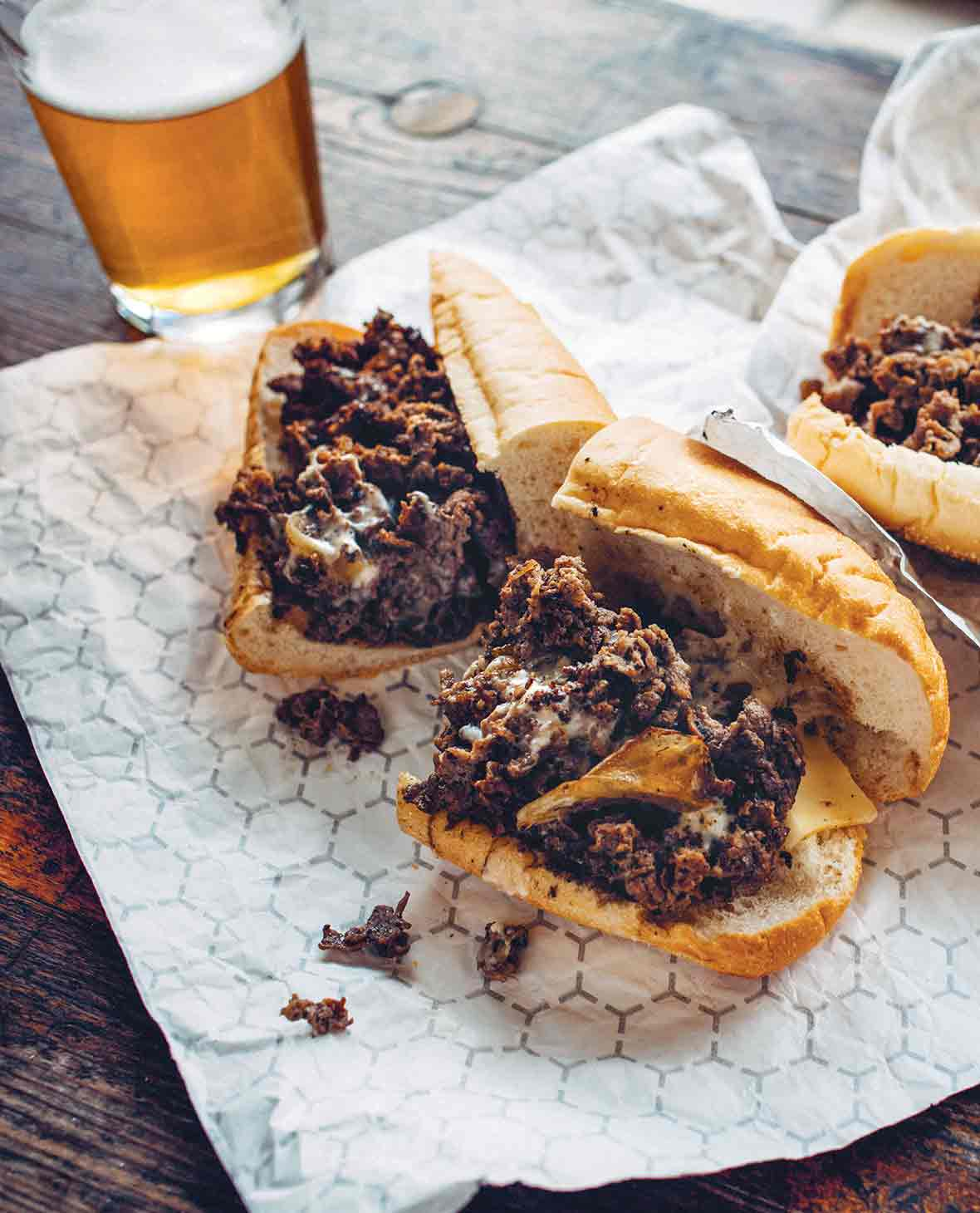 Two Philly cheesesteak sandwiches cut in half on a foil wrapper with a glass of beer in the background.