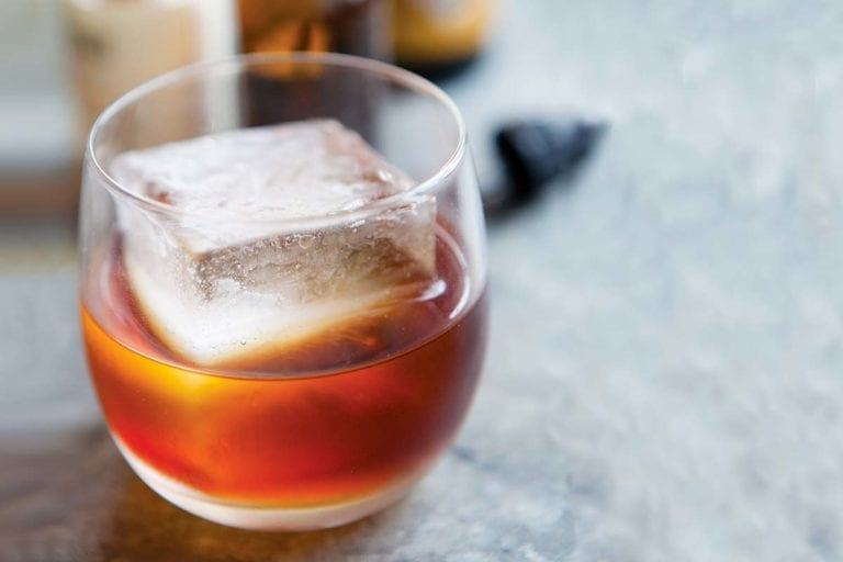 A high ball glass partially filled with an amber Sazerac cocktail without absinthe and an oversized ice cube.