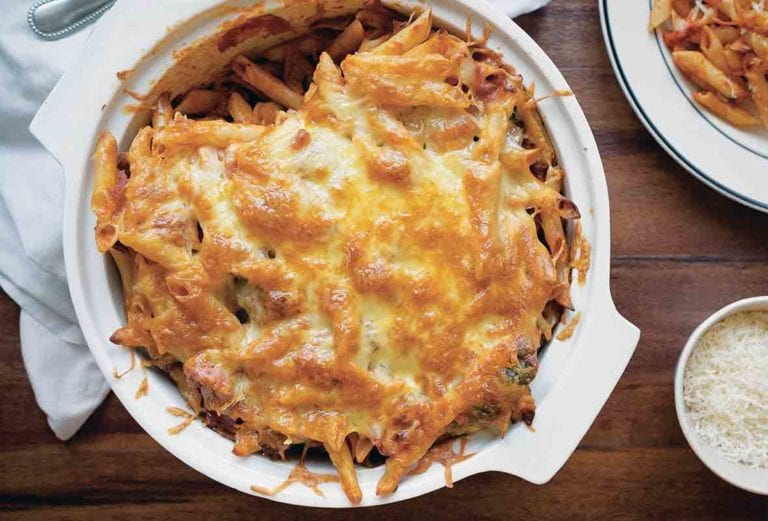 A white round baking dish filled with baked ziti and topped with melted cheese, and a dish of Parmesan on the side.