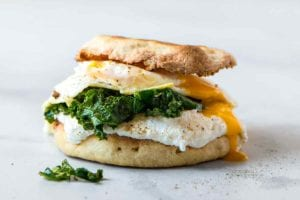 A breakfast sandwich with fried egg, kale, and ricotta sandwiched between two toasted English muffin halves.