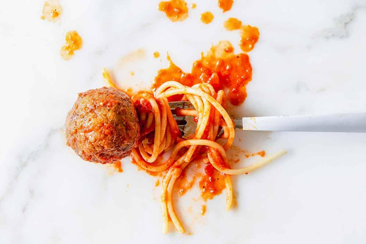 A single eggplant meatball on a fork with spaghetti and tomato sauce.