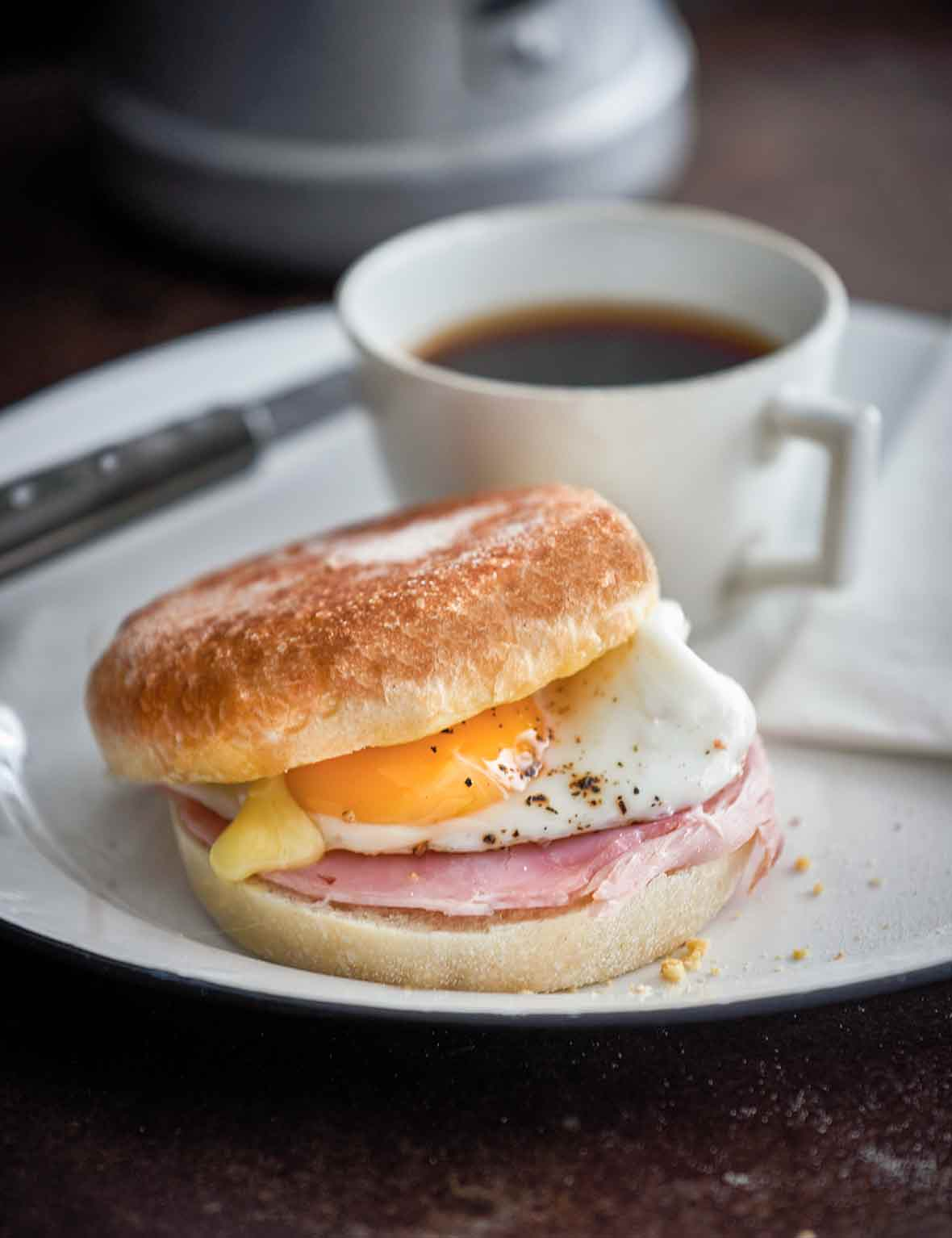 A plate with a breakfast sandwich on a homemade English muffin, a cup of coffee, a knife, and a paper napkin.