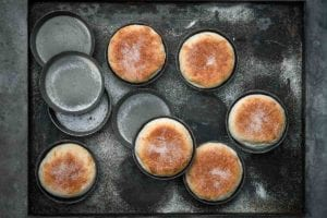 Six homemade English muffins in tins on a baking sheet and four empty tins.