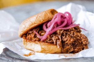 Korean-style sloppy joes made with shredded beef, topped with pickled red onion on a hamburger bun resting on a piece of parchment.