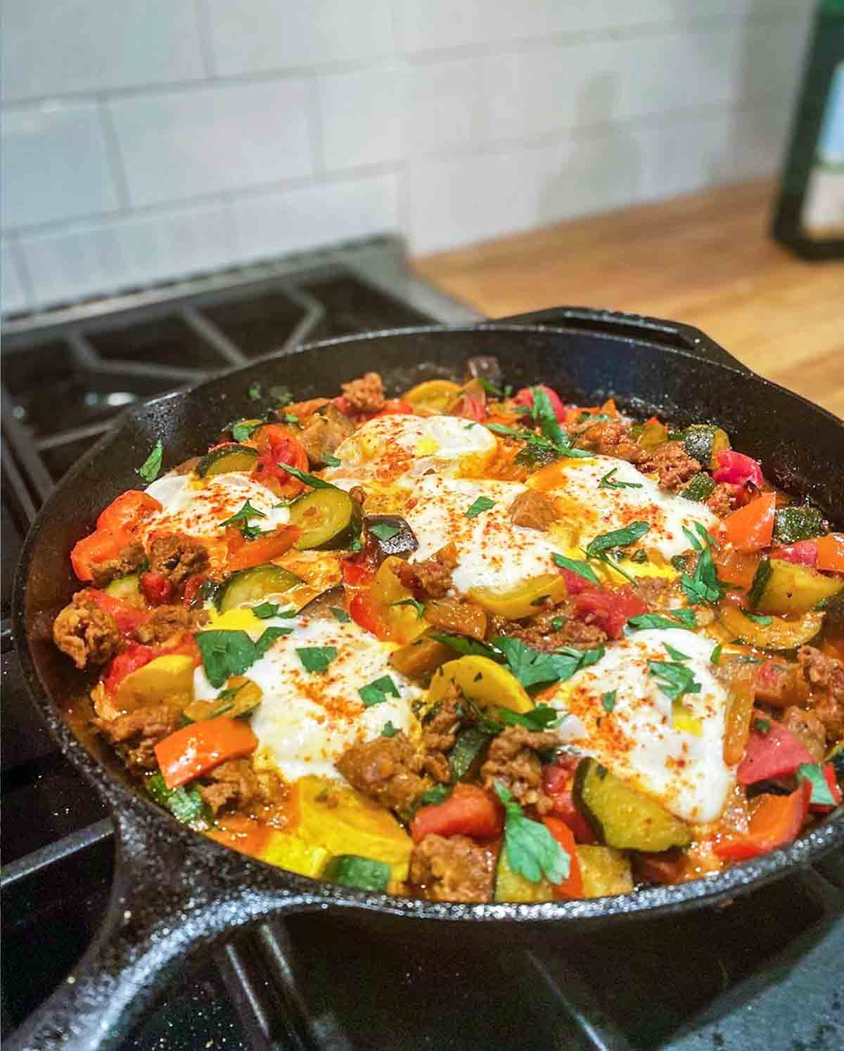 A skillet of eggs with chorizo and eggplant, tomato, zucchini, onion, and peppers.