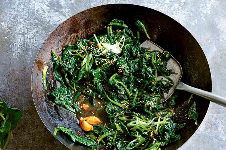 A wok filled with stir-fried spinach with miso and ginger and a colander with fresh spinach beside the wok.