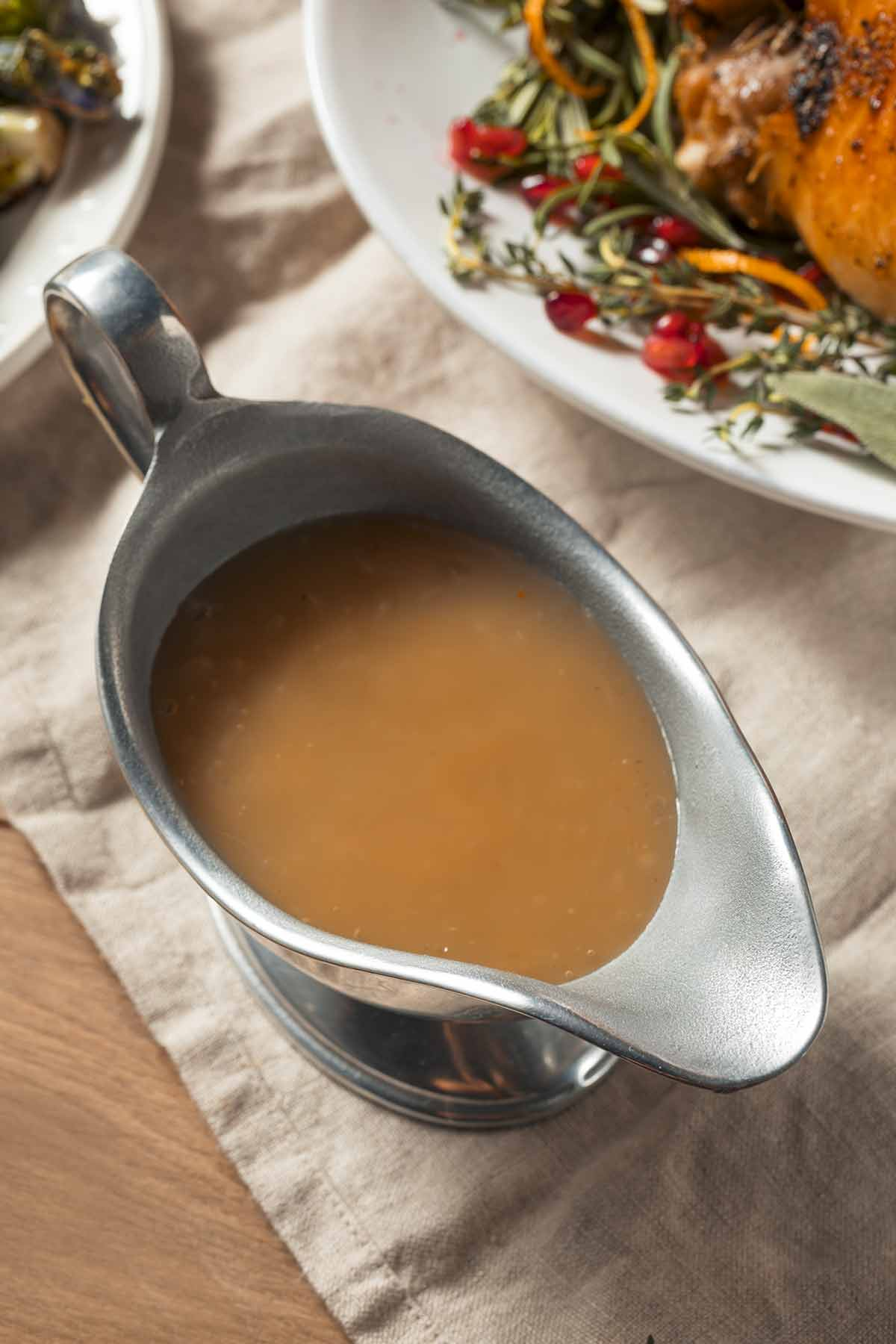 A silver gravy boat filled with gluten-free gravy on a linen cloth.