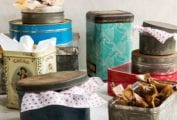 An assortment of holiday cookie tins with tissue paper sticking out of them..