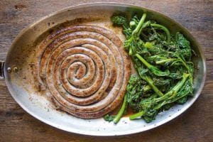 A large coil of Italian sausage and broccoli rabe in an oval skillet.