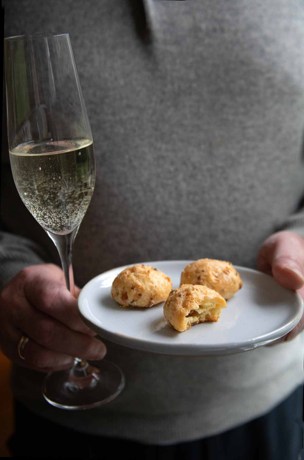 A man holding a glass of Prosecco and a plate with three gougeres.