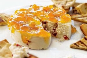 A round of red pepper cheesecake, topped with apricot jam and surrounded by crackers.