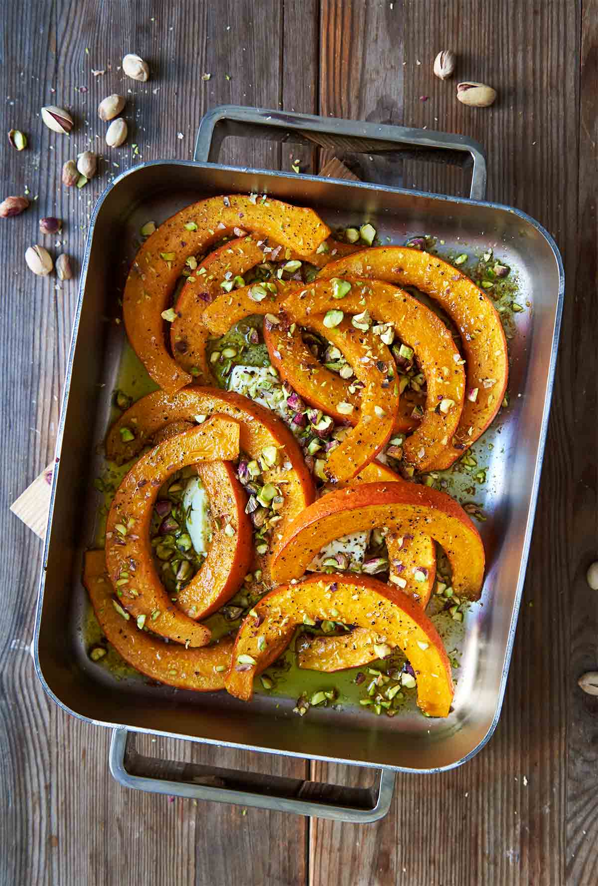 A metal roasting pan filled with roast squash, feta, and pistachios on a wooden table with pistachios scattered around it.