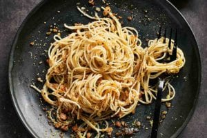 A black plate topped with angel hair pasta with lemon bread crumbs and a fork and a squeezed half lemon rests beside the plate.