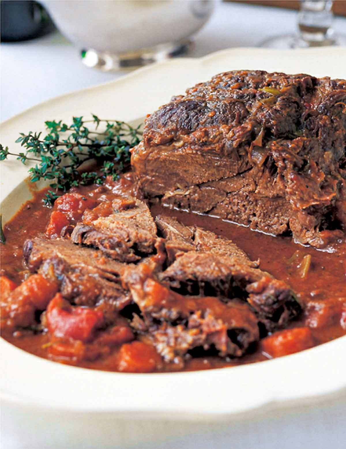 A partially sliced Barefoot Contessa company pot roast on a serving platter, garnished with thyme sprigs.