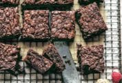 A batch of five ingredient Nutella brownies cut into squares on a wire rack with fresh raspberries scattered around.