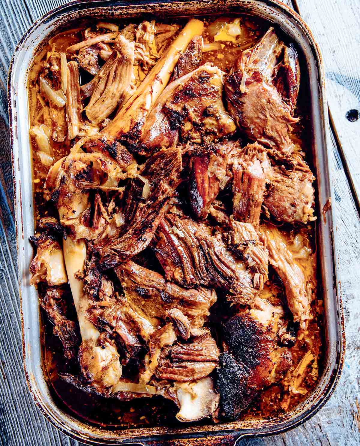 A deep roasting pan filled with shredded lamb barbacoa.
