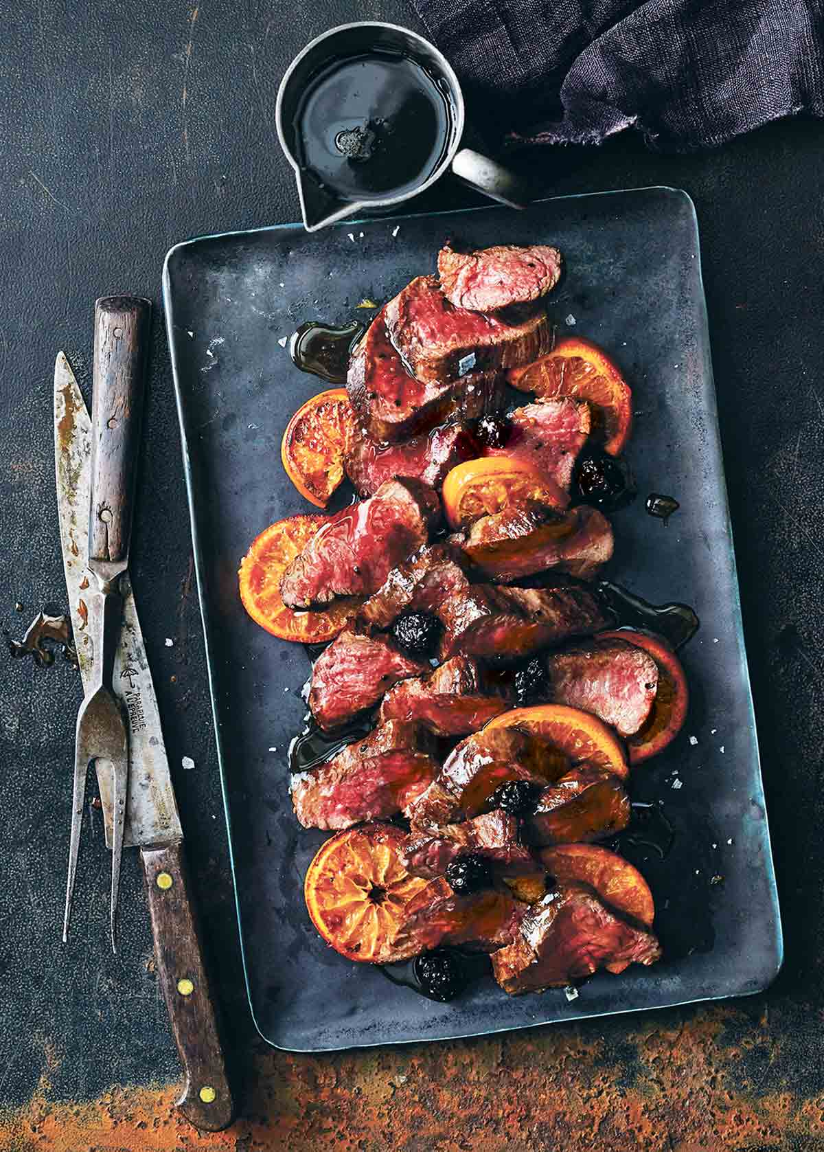 A black tray with sliced roasted venison with balsamic blackberry sauce and sliced oranges.