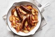 A white enamel cast-iron skillet filled with sautéed sausages with apples on a grey linen cloth.