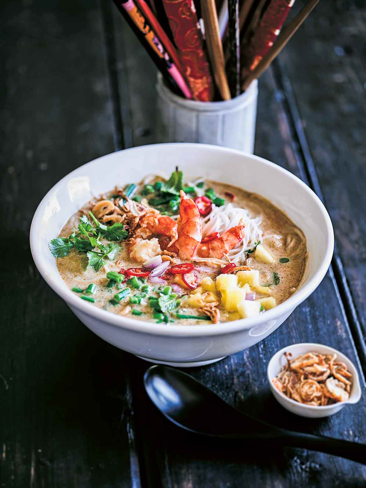 A white bowl of shrimp laksa soup with a small bowl of crispy fried shallots, a spoon, and a container of chopsticks on the side.