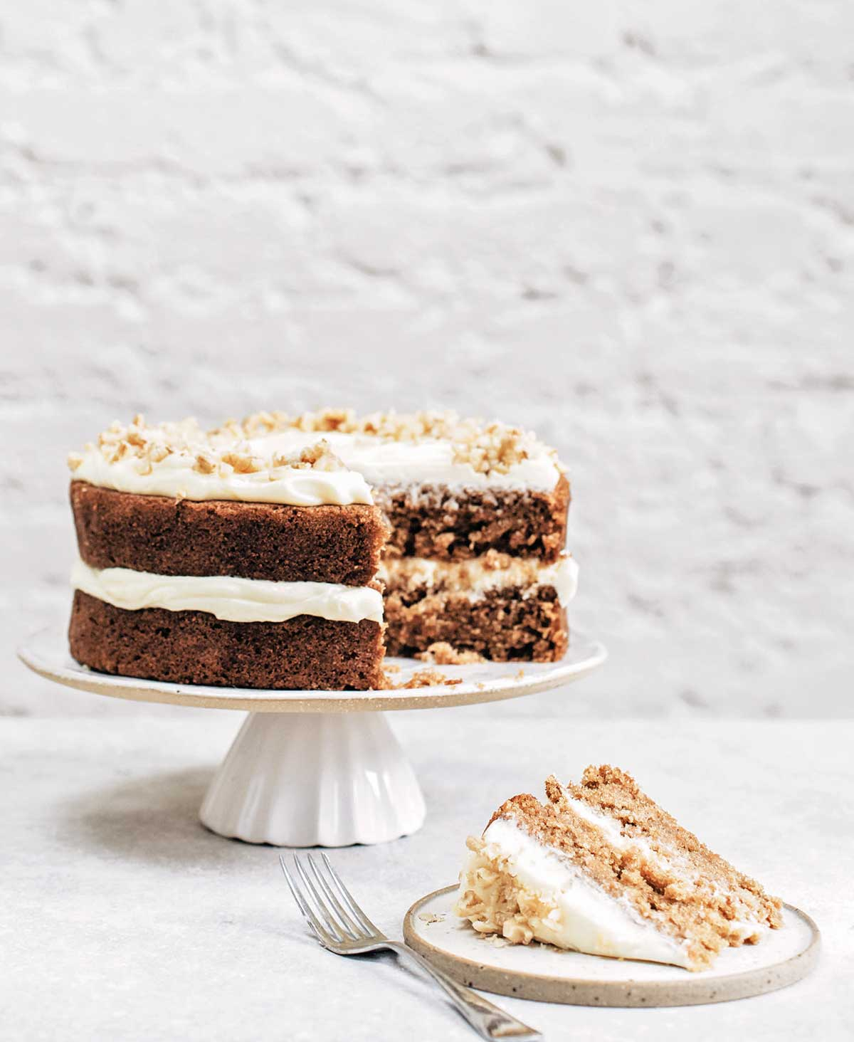 A whole two layer spiced carrot cake on a white cake stand with one slice cut from it on a plate with a fork beside it.