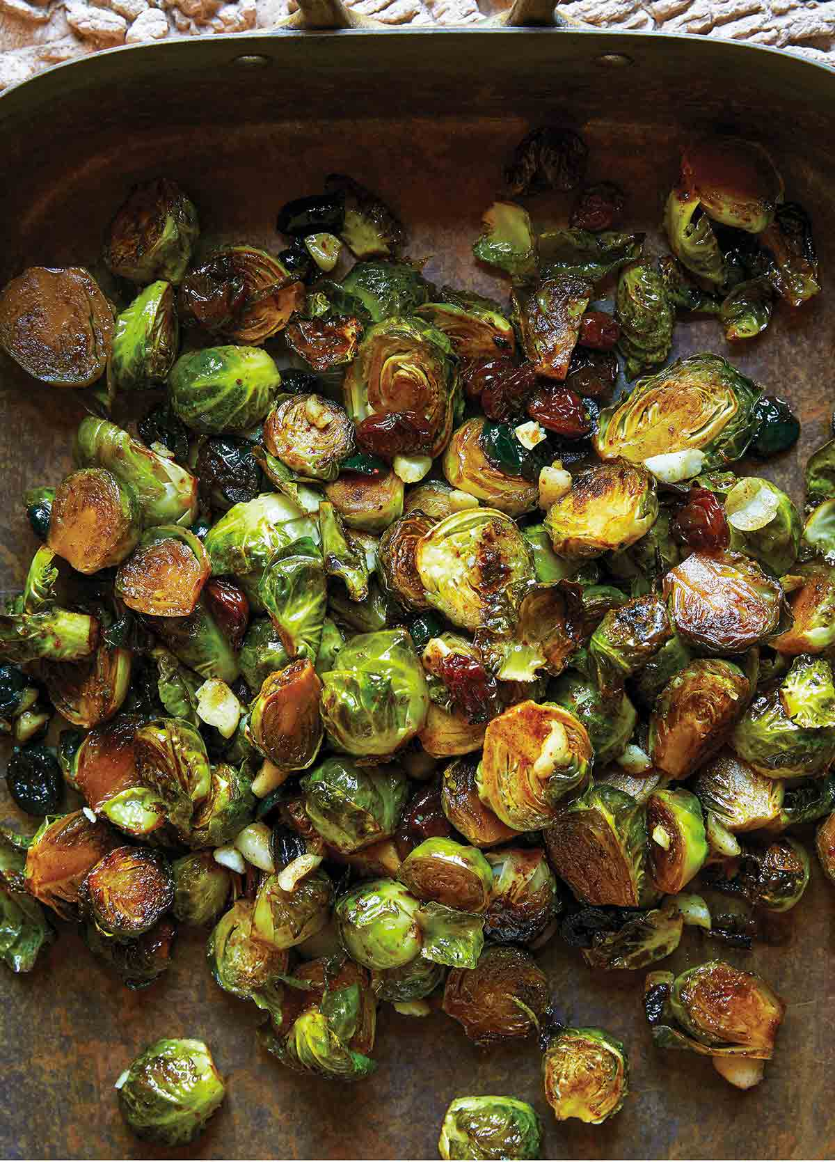 A roasting pan filled with spicy roasted Brussels sprouts, dried cranberries, and a sprinkling of macadamia nuts.