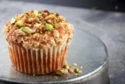 A single apple spice muffin with streusel and pistachios on an inverted metal cake tin.